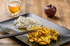 Curta el pollo y el arroz oriental en un plato Imagen de archivo