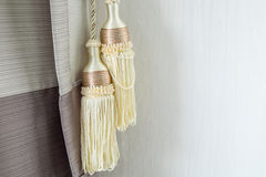 Curtain decorative tassel. Detail shot with a yellow curtain decorative tassel royalty free stock images