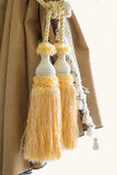 Curtain decorative tassel. Detail shot with a yellow curtain decorative tassel royalty free stock photo