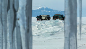 Curtain of icicles and tourist expedition on Baikal ice. Beautiful winter landscape Stock Photography