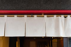 The curtain-like fabric that hangs in front of traditional Japanese restaurants. And shops not only serves as a signboard, but holds a larger meaning stock image
