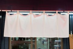 The curtain-like fabric that hangs in front of traditional Japanese restaurants. And shops not only serves as a signboard, but holds a larger meaning stock photography