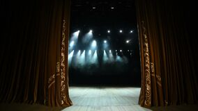 Curtain Opens. Empty theater stage with velvet curtains with spotlights.