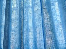 Curtain texture with light shining in. Blue curtain texture with sunlight shining in Royalty Free Stock Photos