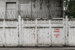 Curtain walls with barbed wire and the inscription restricted area in two language Stock Photos