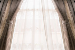Curtain on window. Opened silk curtain in cream color on bright window covering by see through white curtain moving by blowing wind Royalty Free Stock Images