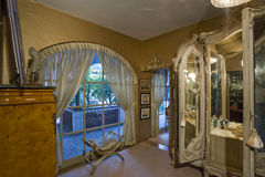 Curtained Arch Window With Dressing Table In Foreground Royalty Free Stock Images