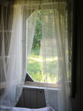 Curtains in the breeze. Old farmhouse window with sheer curtains in the breeze royalty free stock photo
