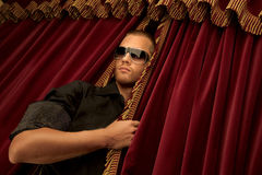 Curtains fall…. A handsome young man wearing sunglasses looking through the curtain Stock Photos