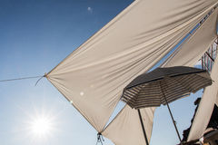 Curtains in the sun. White and blue umbrella with curtains in a sunny sky Royalty Free Stock Image