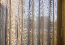 Curtains of a window in the morning. Sunrise through transparent yellow curtains of a window in the morning Stock Images