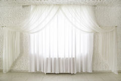 Curtains on windows. White draped curtains on the window in the interior. interior Design Stock Image