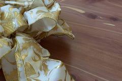 Curva branca e metálica do Natal do ouro no fundo de madeira da grão Fotografia de Stock