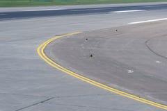 Curva de la pista en el aeropuerto con la línea doble amarilla Foto de archivo libre de regalías