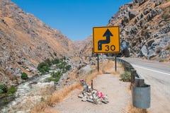 Curva de la señal de tráfico del camino en montañas con límite de velocidad Fotografía de archivo