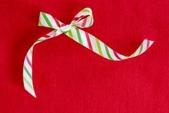 A curva de seda listrada branca, vermelha e verde do feriado no vermelho sentiu o backgr Fotografia de Stock