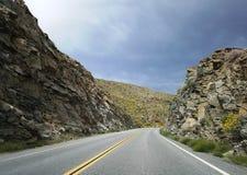 Curva del camino a través de las montañas en el desierto de California Imagenes de archivo