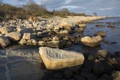 Curva del litorale con i massi e la ghiaia lungo il litorale di Connecticut fotografie stock