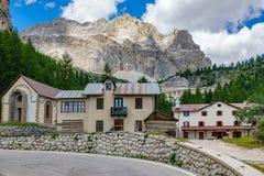 Curva del passaggio di Falzarego con le case, alpi della dolomia, Italia Immagini Stock