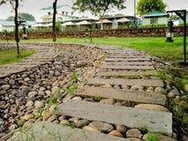Curva del percorso di pietra che conduce ad alcuni cottage Fotografie Stock