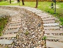 Curva del percorso di pietra nel campo erboso Fotografia Stock