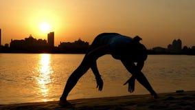 Curva delantera Ancho-Legged de la actitud de la yoga de la práctica de la muchacha la acción en la puesta del sol en