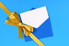 Curva do presente do ouro com o cartão de Natal no fundo azul Fotos de Stock Royalty Free