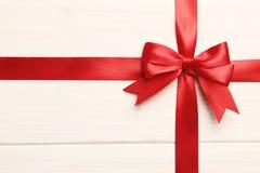 Curva e fita vermelhas do presente em um fundo de madeira branco fotografia de stock royalty free