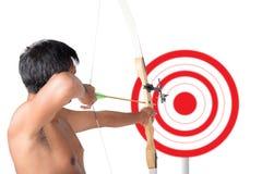 Curva e tiro asiáticos da terra arrendada do homem ao alvo do tiro ao arco Fotos de Stock