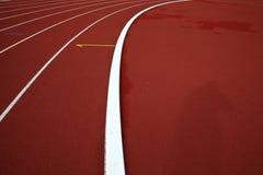 Curva em uma pista de atletismo vermelha Fotos de Stock Royalty Free