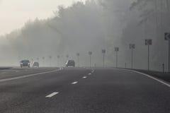 Curva en camino Torneado de las señales de tráfico niebla fotos de archivo