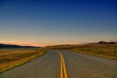 Curva na estrada no crepúsculo Fotografia de Stock Royalty Free
