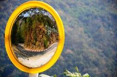 Curva refletindo da estrada do espelho convexo na montanha imagens de stock