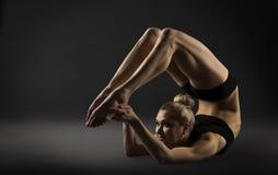 Curva trasera que estira la postura, gimnasia de doblez del acróbata de la mujer Imagen de archivo
