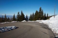 Curva vacía del camino de la montaña en las montañas con los árboles y la nieve de pino Fotografía de archivo