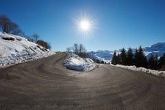 Curva vacía grande del camino de la montaña en las montañas con nieve en lados Foto de archivo libre de regalías