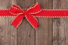 Curva vermelha do Natal e beira superior da fita na madeira velha imagem de stock
