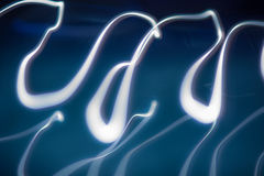 Curvaceous light painting with long exposure trails in cool blue colours Stock Photography