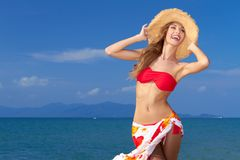 Curvaceous woman in bikini. Glamorous laughing curvaceous woman in bikini and sunhat posing in front of the ocean with her long blonde hair and sarong Royalty Free Stock Image