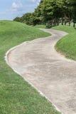 Curvando o campo de golfe verde do caminho e a cena bonita da natureza Fotografia de Stock