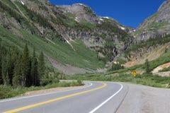 Curvas da estrada da montanha na frente das grandes montanhas em Colorado foto de stock