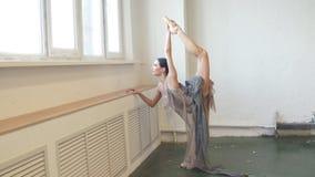 Curvas de la bailarina detrás, colocándose en una pierna que hace estirar, pierna de elevación encima de alto almacen de metraje de vídeo