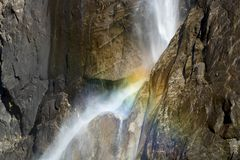 Curvas de la cascada a través del acantilado del granito con el arco iris foto de archivo