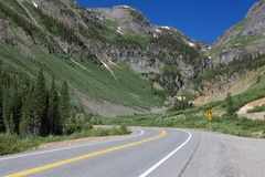 Curvas del camino de la montaña delante de las montañas grandes en Colorado foto de archivo