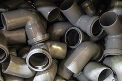 Curvaturas de tubulação plásticas em uma pilha Produtos industriais para a construção fotografia de stock royalty free