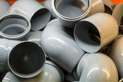 Curvaturas de tubulação plásticas em uma pilha Produtos industriais para a construção fotos de stock