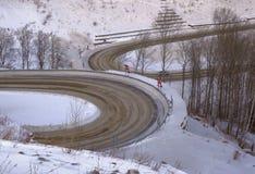 Curvaturas divergentes da estrada na paisagem do inverno foto de stock