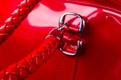 curvaturas, fechos, z?peres, bolsos, prendedores, encaixes e emendas na bolsa vermelha da laca imagem de stock