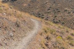 Curvaturas secas da fuga em torno do monte do deserto foto de stock