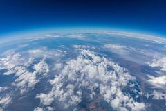 Curvature of planet earth. Aerial shot. Blue sky and clouds. Over land stock image